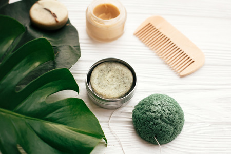 Natural eco friendly solid shampoo bar, wooden brush, deodorant,soap, konjaku sponge on white wood with green monstera leaves. Zero waste products plastic free Stock fotó