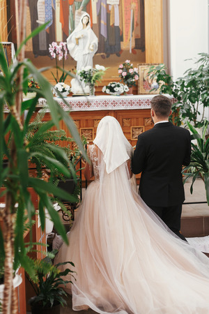 Bride and groom praying, standing on knees at Virgin Mary statue during wedding ceremony. Spiritual couple. Wedding matrimony in church. Emotional romantic moments