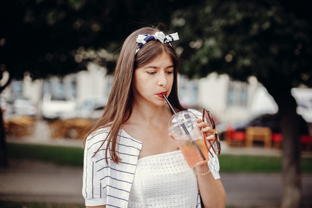 Happy hipster girl in retro dress and headband, holding plastic cup and straw, drinking lemonade. Beautiful stylish young woman holding drink and relaxing in city street