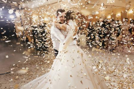 Prachtige bruid en stijlvolle bruidegom dansen onder gouden confetti bij huwelijksreceptie. Gelukkig huwelijkspaar die eerste dans in restaurant uitvoeren. Romantische momenten