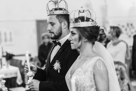 Bride and groom in golden crowns standing with candles in hands during wedding ceremony. Spiritual couple. Wedding matrimony in church. Emotional romantic moments