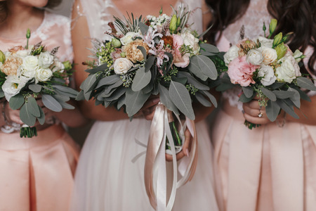 Bridesmaids and bride holding modern wedding bouquets of pink roses and green eucalyptus with pink ribbons. Stylish Contemporary bouquets on soft fabric. Wedding arrangements Stock Photo