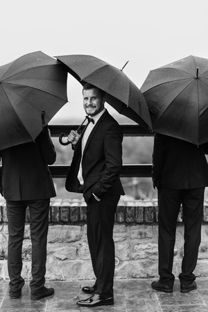 Stylish groom and groomsmen standing under black umbrella and posing. Confident man in suit holding umbrella in rainy outdoors. Rich Businessman and protection concept Stok Fotoğraf