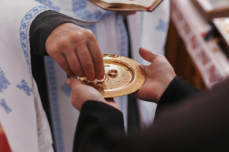 Priest taking golden wedding ring from plate. Wedding matrimony in church. Exchanging wedding rings Stock Photo