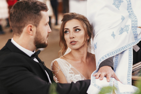 Bride and groom making oaths  and priest holding their hands on holy Bible. Wedding matrimony in church. Exchanging vows. Emotional romantic moments Stock Photo