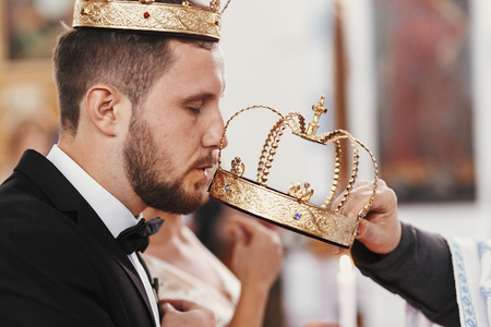 Bride and groom kissing golden crowns from priest hand during wedding ceremony. Spiritual couple. Wedding matrimony in church. Emotional romantic moments