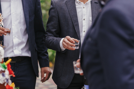 Stylish man holding glasses of vodka and toasting at wedding reception. Corporate businessman cheering with alcohol drinks at party outdoors. Christmas feast Stock Photo