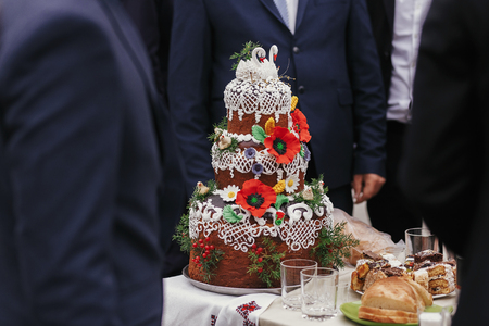 Traditional ukrainian wedding cake bread, decorated with flowers poppy and swans on top. Wedding cake Standard-Bild - 113443146