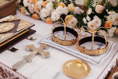 Holy matrimony in church. Golden crowns,cross,bible and candles on altar in church, religious items