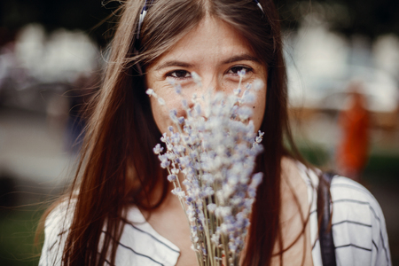 Happy hipster girl enjoying aroma of lavender bouquet. Calm atmospheric moment. Beautiful stylish young woman holding amazing lavender flowers and smelling them in sunny outdoors.