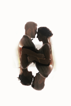 Gorgeous bride and stylish groom silhouettes gently hugging. Double exposure of sensual wedding couple embracing. Romantic moments of newlyweds. Creative wedding photo