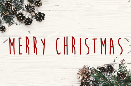 Merry Christmas text on modern christmas flat lay with green fir branches, golden pine cones and stars. Season's greetings card. Happy Holidays and Happy new year
