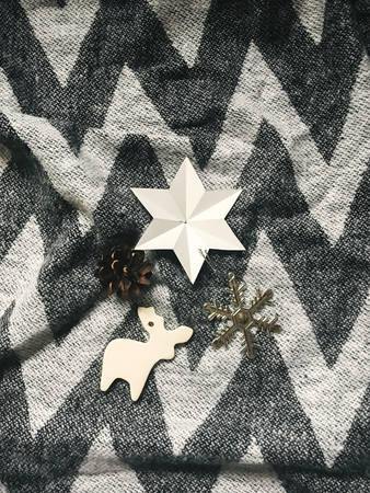 Holiday ornaments, stylish christmas reindeer ,star,snowflake toy on rustic blanket. Top view. Atmospheric cozy image, warm winter mood. Mobile Photo Stock Photo