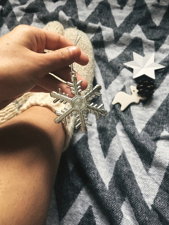 Hand holding stylish christmas snowflake on background of christmas woolen socks on legs, holiday ornaments on rustic blanket.  Atmospheric cozy image, warm winter mood. Mobile Photo