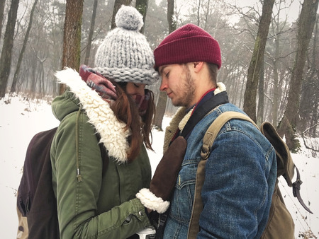 Happy hipster couple in stylish outfits embracing and hugging in snowy winter park. Cute family taking selfie. Atmospheric cozy winter moments. Moody image Stock Photo