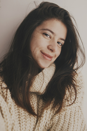 Portrait of young attractive woman with no makeup in knitted sweater smiling in soft light in room. Stylish hipster girl taking selfie. Atmospheric cozy winter moments. Moody image, carefree