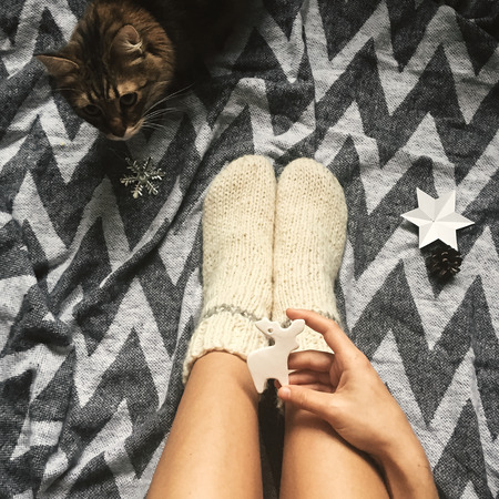Cute cat playing with holiday ornaments at girl legs in christmas woolen socks and stylish reindeer toy in hands. Top view. Atmospheric cozy image, warm winter mood. Mobile Photo