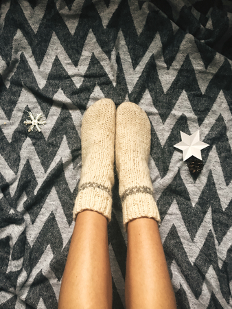 Stylish christmas woolen socks on woman legs, relaxing on plaid with holiday ornaments in festive room. Top view. Atmospheric cozy image, warm winter mood Stock Photo