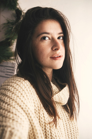 Stylish hipster girl in knitted sweater smiling in soft light in room. Portrait of young attractive woman relaxing and taking selfie. Atmospheric cozy winter moments. Moody image