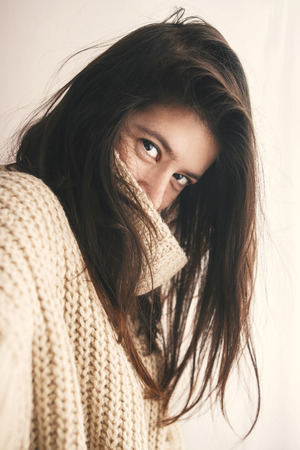 Portrait of young attractive woman with no makeup and gorgeous hair in knitted sweater smiling in soft light in room. Stylish hipster girl taking selfie.