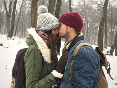 Happy hipster couple in stylish outfits embracing and kissing in snowy winter park. Cute family taking selfie. Atmospheric cozy winter moments. Moody image