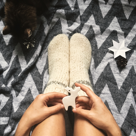Christmas woolen socks on legs and woman holding stylish reindeer toy, and cute cat  playing with holiday ornaments in festive room.