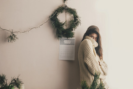 Stylish hipster girl in knitted sweater smiling in rustic room on background of handmade christmas wreath and lights.