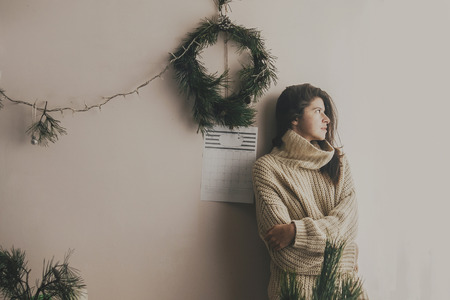 Stylish hipster girl in knitted sweater posing in rustic room on background of handmade christmas wreath and lights.