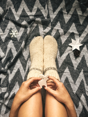 Christmas woolen socks on legs and woman holding stylish reindeer toy, relaxing on plaid with holiday ornaments in festive room. Stock Photo