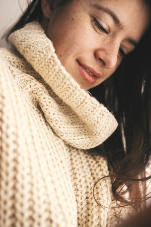 Stylish hipster girl in knitted sweater smiling in soft light in room. Portrait of young attractive woman relaxing and taking selfie.