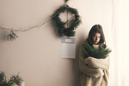 Stylish hipster girl in knitted sweater standing in rustic room and holding branches of fir on background of handmade christmas wreath and lights. Stock Photo