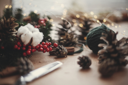 Fir branches, wreath, red berries, pine cones, thread, scissors, cinnamon, cotton, lights on rustic wooden background. Details for making christmas wreath at workshop. Atmospheric image