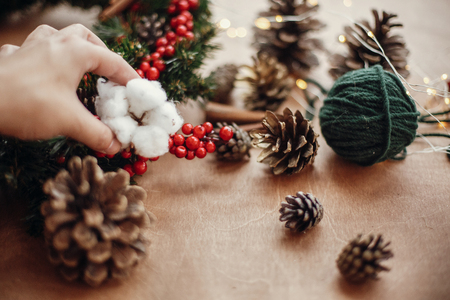 Hand putting cotton on wreath,pine cones, fir branches, red berries, thread, cinnamon,  lights on rustic wooden background. Details for making christmas wreath at workshop. Atmospheric image Banco de Imagens