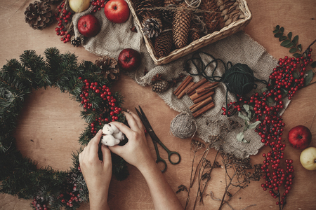 Rustic Christmas wreath flat lay. Hands putting cotton on fir branches, red berries and pine cones,thread, scissors, cinnamon on rustic wooden background. Making wreath at holiday workshop