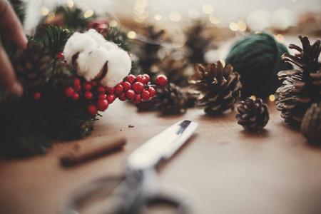 Tannenzweige, Kranz, rote Beeren, Tannenzapfen, Faden, Schere, Zimt, Baumwolle, Lichter auf rustikalem Holzhintergrund. Details für die Herstellung von Weihnachtskranz in der Werkstatt. Stimmungsvolles Bild