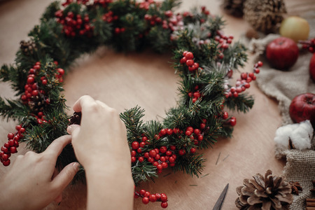 Rustic Christmas wreath. Hands holding fir branches, red berries and pine cones,rope, scissors, cinnamon, cotton on rustic wooden background. Atmospheric moody image at holiday workshop Foto de archivo - 113323521