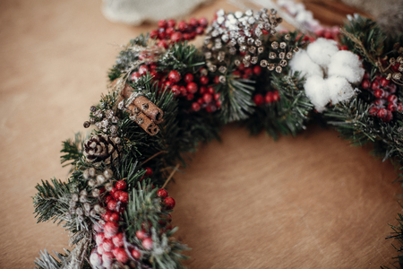 Details of rustic Christmas wreath. Fir branches with red berries,pine cones,ribbon, cinnamon,cotton  on rustic wood. Atmospheric moody image at holiday workshop