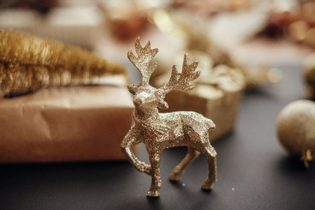 Christmas gold reindeer and gift box with tree on background of glitter baubles on stylish black table. Modern Christmas image . Seasons greetings card. Merry Christmas and Happy New Year