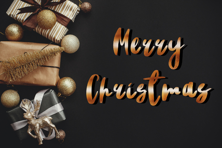 Merry Christmas text, handwritten golden sign at christmas border of gift boxes ,tree ,reindeer and glitter baubles on stylish black background. Seasons greetings card