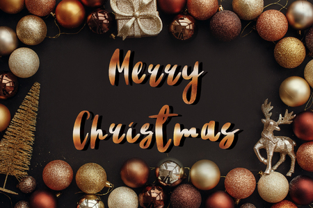 Merry Christmas text, handwritten golden sign at christmas gold frame of gift box, tree, reindeer and glitter baubles on stylish black background. Seasons greetings card