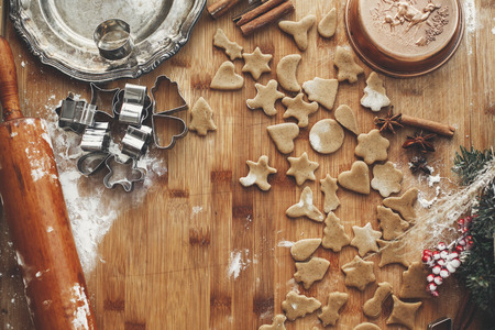 Making christmas gingerbread cookies flat lay. Dough with metal cutters on rustic table with wooden rolling pin, cinnamon ,anise, cones, christmas decorations. Atmospheric stylish image