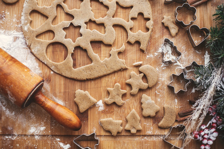 Christmas cookies Flat lay. Dough with metal cutters on rustic table with wooden rolling pin, cinnamon ,anise, cones, christmas decorations. Making cookies, atmospheric image