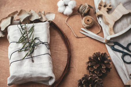 Stylish rustic gift wrapped in linen fabric with green branch on wooden table with pine cones,wreath,tree, reindeer, scissors, twine, cotton. Simple eco presents plastic free. Zero waste holidays 免版税图像