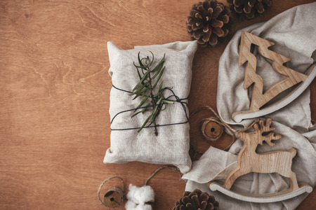 Simple eco presents plastic free. Zero waste  holidays. Stylish christmas rustic gift wrapped in linen fabric with green branch on wooden table with pine cones, tree,reindeer, twine, cotton. Flat lay.