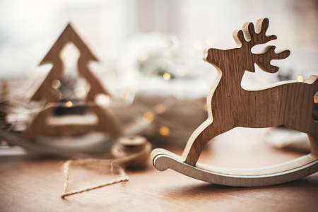 Rustic reindeer christmas toy on wooden table on background of wooden tree,lights, twine, gift in linen fabric with green branch, pine cones. Simple eco presents. Zero waste holidays