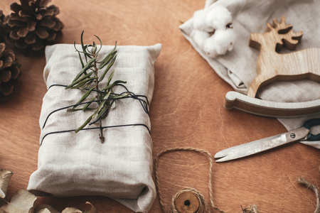 Zero waste  holidays.  Stylish christmas rustic gift wrapped in linen fabric with green branch on wooden table with pine cones, reindeer, scissors, twine, cotton. Simple eco presents plastic free.