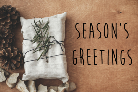 Seasons greetings text sign on stylish christmas rustic gift wrapped in linen fabric with green branch on wood with pine cones. Seasonal greeting card. Eco present. Atmospheric image