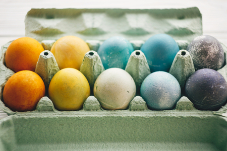 Stylish easter eggs in carton tray on white wooden background. Modern colorful easter eggs painted with natural dye in different colors. Happy Easter, eco concept