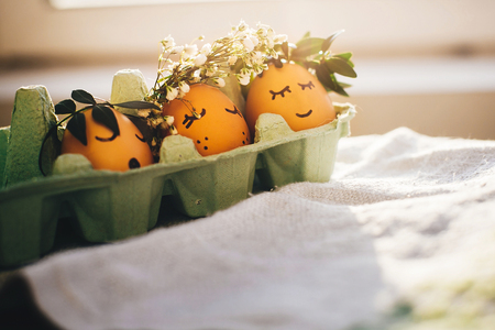 Stylish easter eggs in floral wreaths and  cute faces in carton tray. Modern cute easter eggs with flowers crown and sleepy eyes in sunny light. Happy Easter,  rustic eco concept. Space for text
