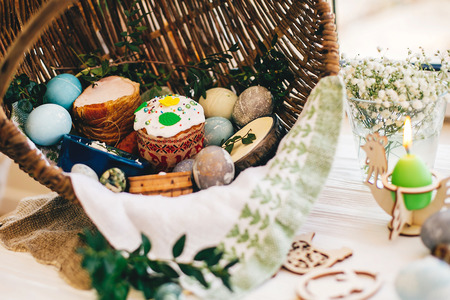 Traditional Easter basket with stylish eggs, easter bread, ham, sausage, butte, and flowers, candle on rustic wooden background. Happy Easter concept. Traditional food in rustic basket